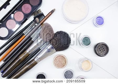 Decorative cosmetics for a festive party. Isolated on white background. A palette of colored shiny eye shadow. Brushes. Close-up.