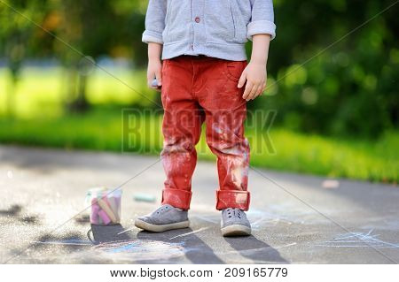 Close-up Photo Of Little Kid Boy Drawing With Colored Chalk On Asphalt