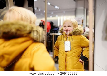 Cute Little Boy Trying New Coat During Shopping