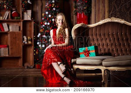 Holidays, celebration and people concept - young smiling woman in elegant red dress over christmas interior background.