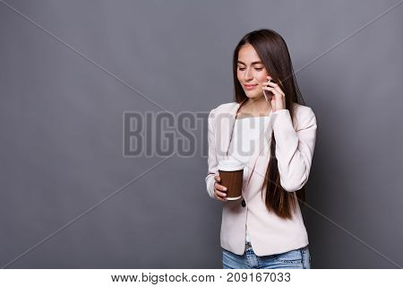 Busy elegant business woman in formal suit talks on mobile and drinks coffee. Conversation concept, gray studio background, copy space