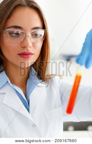 Technician hold in arms in protective gloves sample bottle with poison fluid portrait. Medical worker in uniform use reagent tube for virus infection exam or biological toxic reaction, drug creation