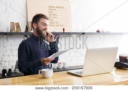 Surprised bearded barman with laptop and papers at bar counter. Bartender working with computer, documents and mobile. Online purchase, technology, coffee business and service concept, copy space