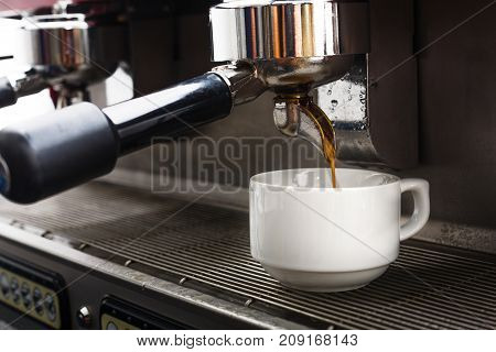 Coffee machine preparing hot bracing beverage. Espresso pouring into white porcelain cup. Small business and professional coffee brewing concept