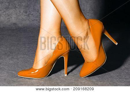 Female legs in orange socks and orange high heels shoes.