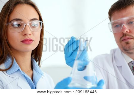 Technicians hold in arms sample bottle with fluid and drop reagent with pipet portrait. Medical worker in uniform use reagent tube for virus infection exam or biological toxic reaction, drug creation