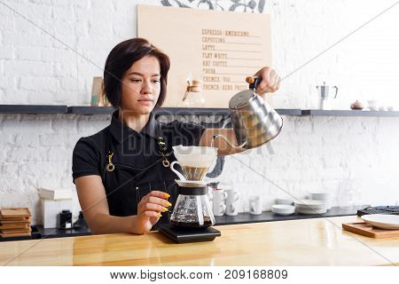 Barista preparing pourover coffee at cafe counter. Portrait of young girl in uniform at her working place. Small business, occupation people and service concept, copy space