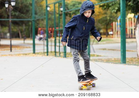 Little Urban Boy With A Penny Skateboard. Kid Skating In An Autumn Park. City Style. Urban Kids.