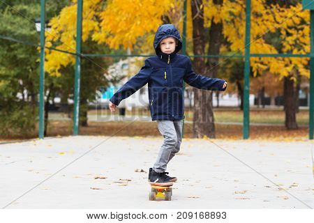 Kid Skating In An Autumn Park. City Style. Urban Kids. Child Learns To Ride A Penny Board
