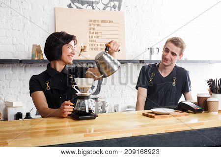 Coffee business backgroung with copy space. Portrait of two young bartenders preparing fresh pourover coffee at cafe bar counter. Occupation people and service concept