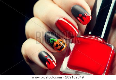Halloween manicure design ideas. Halloween Nail art design. Nail Polish. Beauty Trendy Stylish Colorful Nails and Nailpolish. Black matte nailpolish with blood drips and pumpkin. Isolated on black