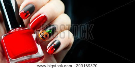 Halloween manicure design ideas. Halloween Nail art design. Nail Polish. Beauty hands. Trendy Stylish Colorful Nails and Nailpolish bottle. Black polish with blood dops and pumpkin. Isolated on black