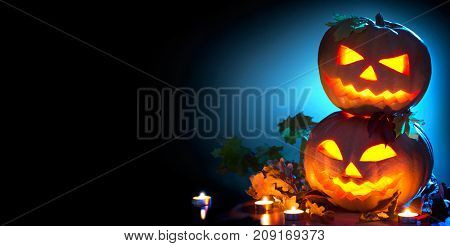 Halloween pumpkin head jack lantern with burning candles over black background. Halloween holidays border art design, celebration. Carved Halloween Pumpkins with burning candles