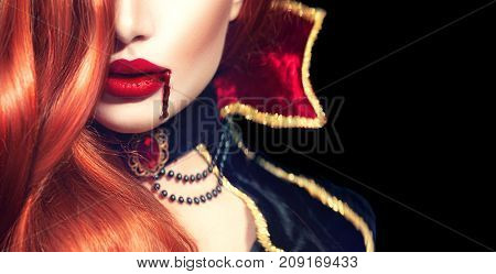 Halloween Vampire Woman sexy lips with dripping blood. Beautiful Glamour Fashion Sexy Vampire Lady with long red hair, beauty make up and costume. Isolated on black background. Vampire mouth