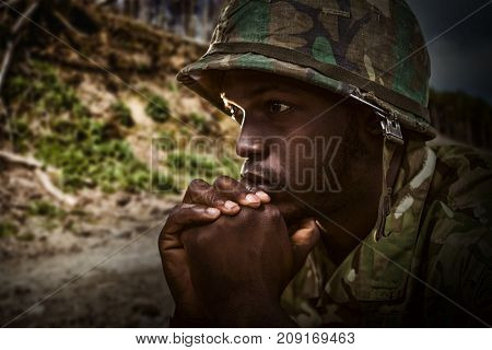 Close up of thoughtful soldier against dirt road on mountain against sky