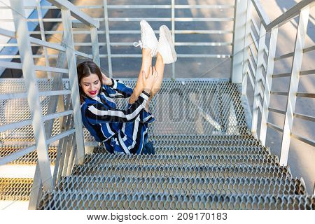 Woman Sitting On The Metal Stairs