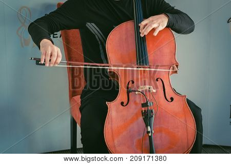 Man sitting on chair and plating cello