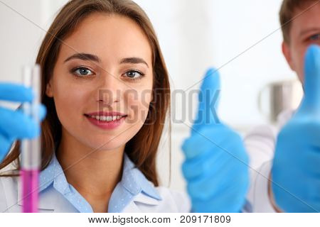 Smiling beautiful technician woman portrait show OK or confirm with thumb up and sample bottle with poison fluid. Medical worker in uniform use reagent tube for virus infection exam in drug creation