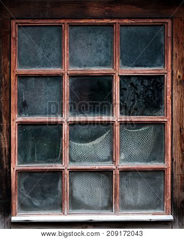 The window of an old, wooden farm house with net inside