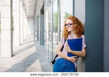 Happy redhead female student in glasses having break between classes. Education and entering the university concept. Copy space on the wall