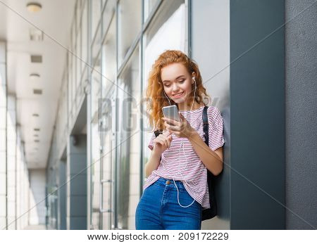 Smiling redhead student girl listening to music online on smartphone in earphones. Leisure, education, studying and entering the university concept
