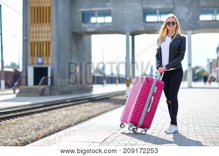 A girl with a pink suitcase is standing at the railway station waiting for her train on a sunny day
