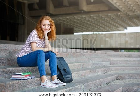 Pensive young redhead female student having a break between classes. Attractive female student sitting on the steps with textbooks and backpack. Education concept