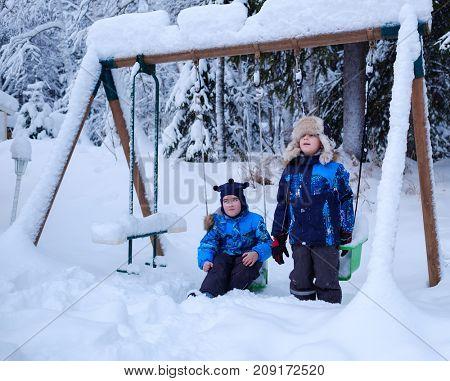 Happy boy on a swings in snowy winter
