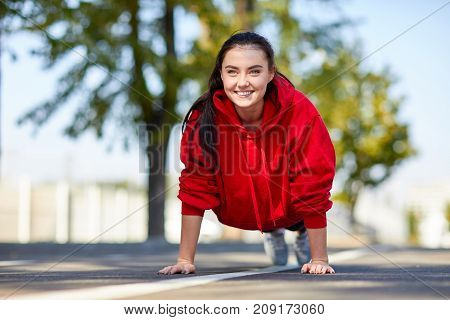Lovely girl in red uniform girl squeezes off the floor in the street