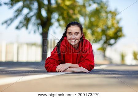 Beautiful girl in a red uniform the girl is lying on her stomach from on the street