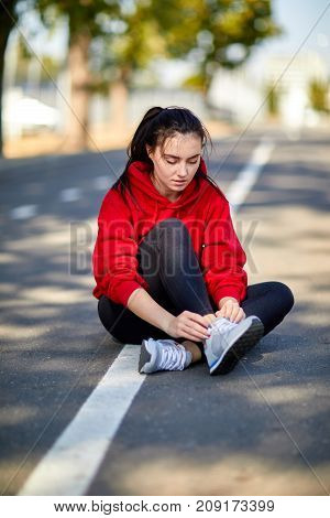 Young beautiful girl sits on the ground in red uniform on a sunny autumn day ties up shoelaces