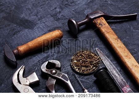 Set of cobbler vintage tools pliers nippers hook sewing cobbler's hammer on the dark wooden background. Top view poster