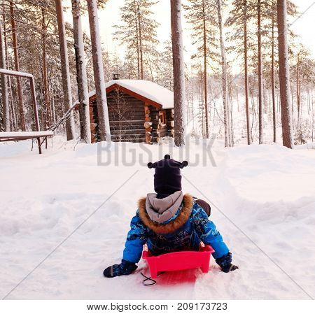 Happy boy riding sledge in snowy winter