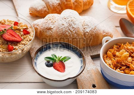 Traditional french breakfast menu closeup. Yogurt with fresh berries, cup of coffee, muesli and croissants on wooden table