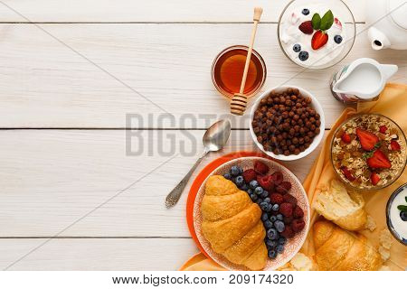 Rich breakfast menu background. French crusty croissants, muesli, yogurt, coffee, berries, honey and boiled eggs for tasty morning meals on wooden table, top view, copy space