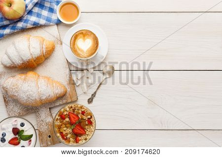 Traditional french breakfast menu background. Yogurt with fresh berries, cup of coffee, muesli and croissants on wooden table, top view, copy space