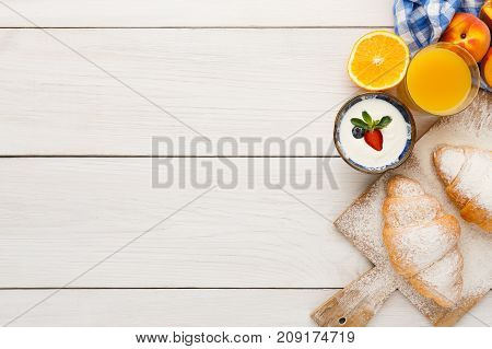 Traditional french breakfast menu background. Yogurt with fresh berries, glass of orange juice, muesli and croissants on wooden table, top view, copy space