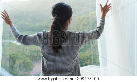 Woman unveil the window curtain at home