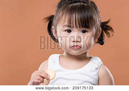 Lovely girl holding biscuit