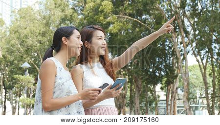 Two young woman finding a place on cellphone