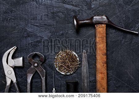 Set Of Cobbler Vintage Tools Pliers Nippers Hook Sewing Cobbler's Hammer On The Dark Wooden Backgrou