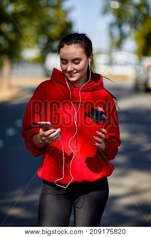 A girl after a warm-up with a refreshing drink on a sunny autumn day with a phone and wearing headphones
