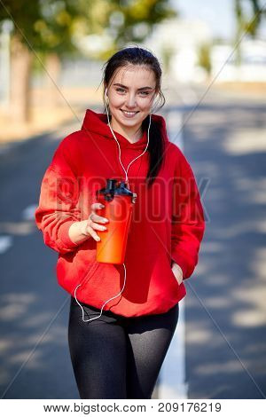 Young, beautiful girl at a warm-up in the street in the park doing muscle stretching