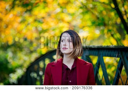 Woman In Red Coat Have A Rest In Autum Park