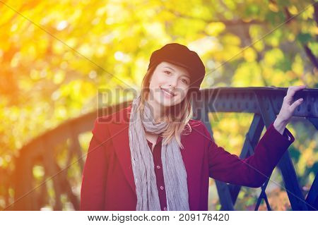 Woman In Red Coat And Hat Have A Rest In Autum Park