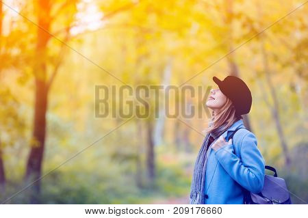 Woman In Blue Coat And Backpack Have A Rest In Autum Park