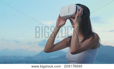 Woman watching on VR device in the evening