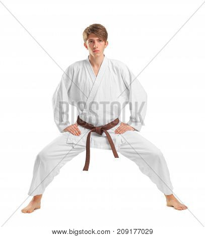 A young guy karate with a brown belt on a white isolated background has become in the fighting stance