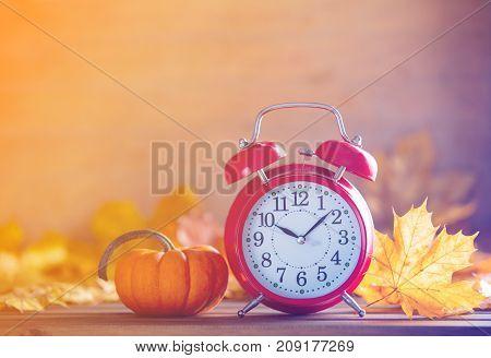 Vintage Alarm Clock And Maple Tree Leaves With Pumpkins