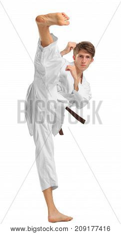 Young guy karatek with a brown belt on white isolated background coaches kicks feet